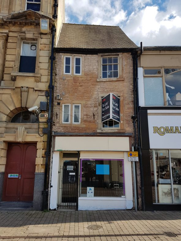 Frontal view of this narrow, three storey building with a stone facade and 20th century shop front.