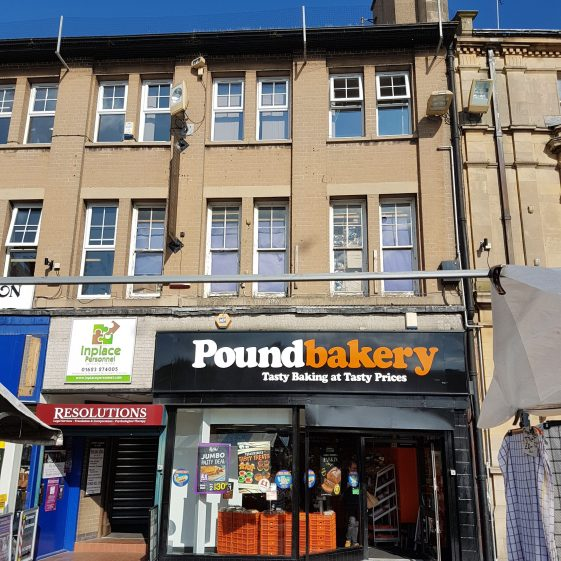 Frontal view of three storey 20th century building with UPVC replacement windows on the second floor and most of the first floor, where two original windows remain. Pound Bakery on ground floor.
