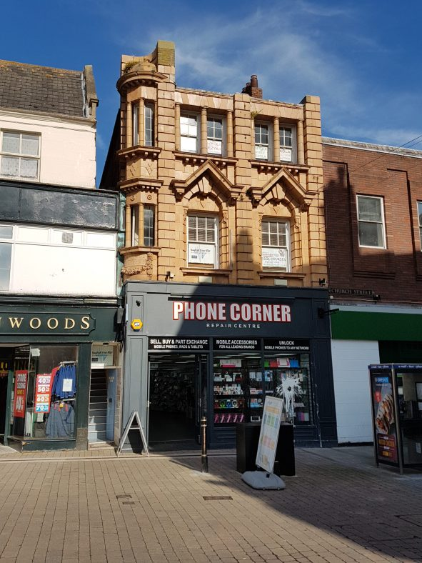 Frontal view of an unusual early 20th century corner building with a glazed terracotta tiled facade. Phone Corner mobile phone shop on the ground floor.