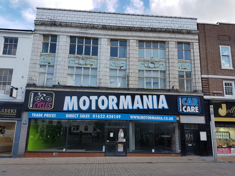 The three storey building has metal window frames and terracotta facades on the first and second floors separated by a decorated cast-iron band. The 20th century shop front at street level is occupied by Motormania Car Care.