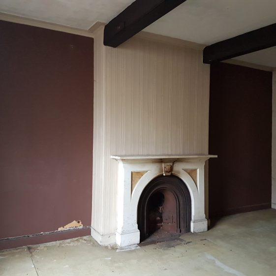 View of interior on upper floor with fireplace and exposed beams