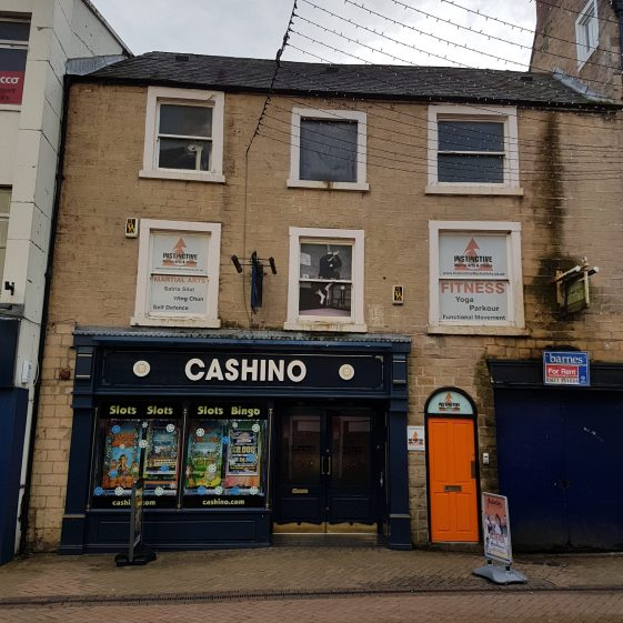 Frontal view of three storey stone building with sash windows and Cashino shop front on ground floor