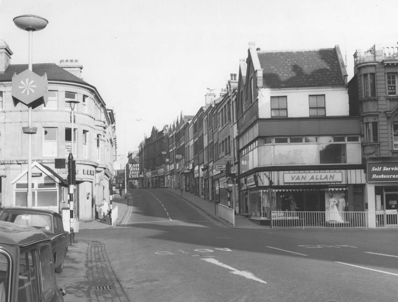 Black and white photo of the view in 1971 from the Market Place up Leeming Street showing 30 Market place on right occupied by Van Allan clothing store.n
