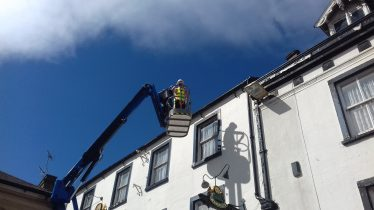 Man in high-viz jacket in cherry picker basket clearing gutters at the 'Market Inn'