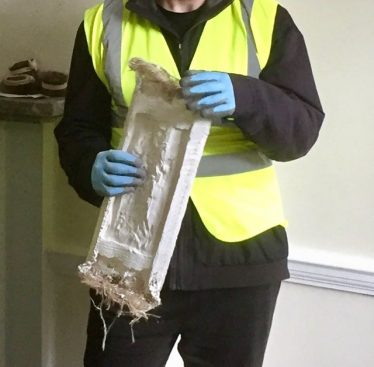 Construction student in high viz waistcoat and gloves holding a piece of plaster ceiling moulding