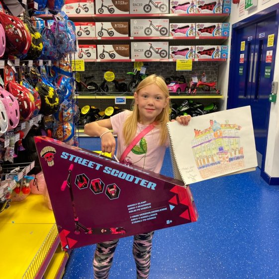 Holly Hopkin, second prize winner at Smyths Toys choosing a Street Scooter!